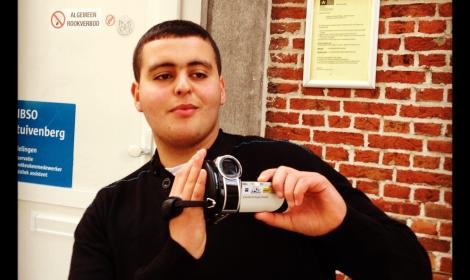 Samir voor de school met een videocamera