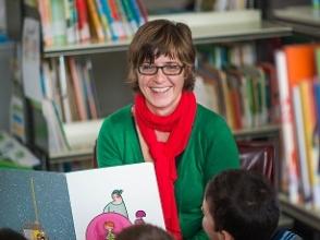 Logopediste leest boek in school bibliotheek met enkele kinderen
