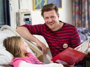Leerkracht geeft les aan ziekenhuisbed
