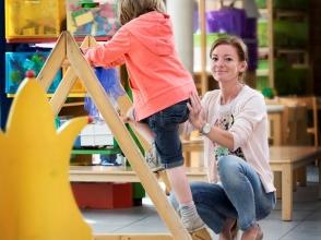 Leerkracht geeft kind een duwtje om op een speeltoestel te geraken