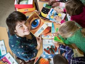 Leerkracht met leerlingen aan tafel met prenten en woorden