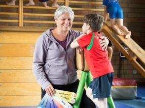 Leerkracht helpt leerling aan turntoestel