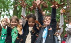 Leerlingen van het Stedelijk Basisonderwijs gooien met herfstbladeren