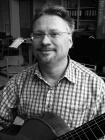 leeraar Academie Deurne met gitaar