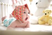 Baby ligt op buik en lacht