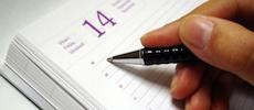 hand met pen schrijft in agenda