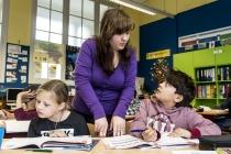 Twee leerlingen luisteren naar de juf in Stedelijke Basisschool De Zonnebloem.