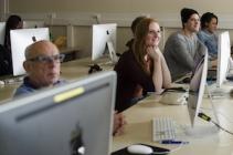 cursisten achter een mac-scherm