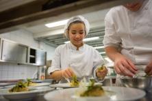 leerling-kok dresseert borden in keuken