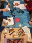 kinderhanden aan tafel met kleurkrijtjes en papapier