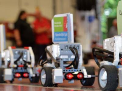 LEGO Mindstorms robots op een rij met vlag van Stedelijk Lyceum Hardenvoort