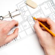 Een architect tekent een plan uit.