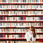 Een meisje zit in een bibliotheek en leest een boek.