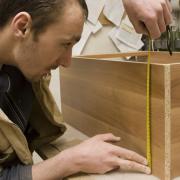 Een jongen maakt een meubelstuk.