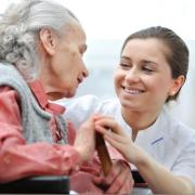 Een meisje helpt een oudere dame.