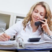 Een meisje beantwoordt een telefoon en schrijft iets in een dossier.