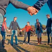 Mensen staan in een kring en houden elkaars hand vast.