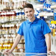 Een jongen helpt klanten verder in een grootwarenhuis.