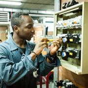 Een jongen repareert een elektriciteitskast.