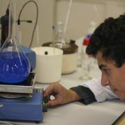 Een jongen onderzoekt een chemische stof in een lab.