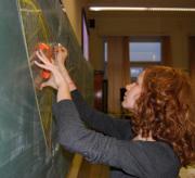 Een meisje berekent de oppervlakte van een figuur.