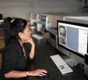 Een meisje ontwerpt een affiche met de computer.