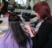 Een meisje knipt de haren van een andere dame.