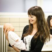 Een meisje houdt een baby vast.